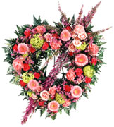 STANDING Eternal Rest Heart Wreat - Share the grief with this resplendent wreath. Pink and purple hues of roses, gerbera daisies, carnations and more are combined in this delicate display. Appropriate to send to the funeral home. Arrangement is delivered with an easel for display. Approx. 29.5H x 2